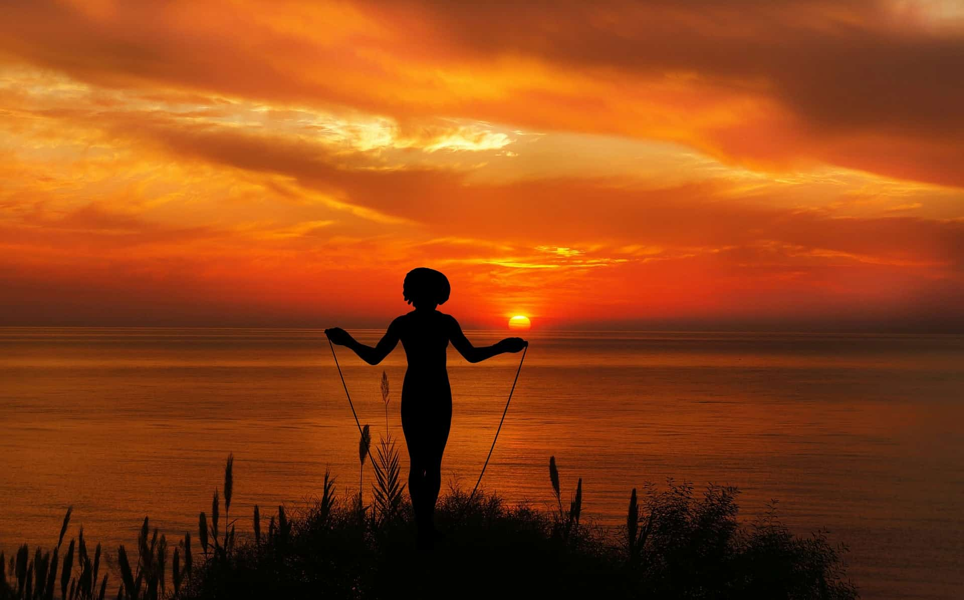 a woman jumping rope at sunset