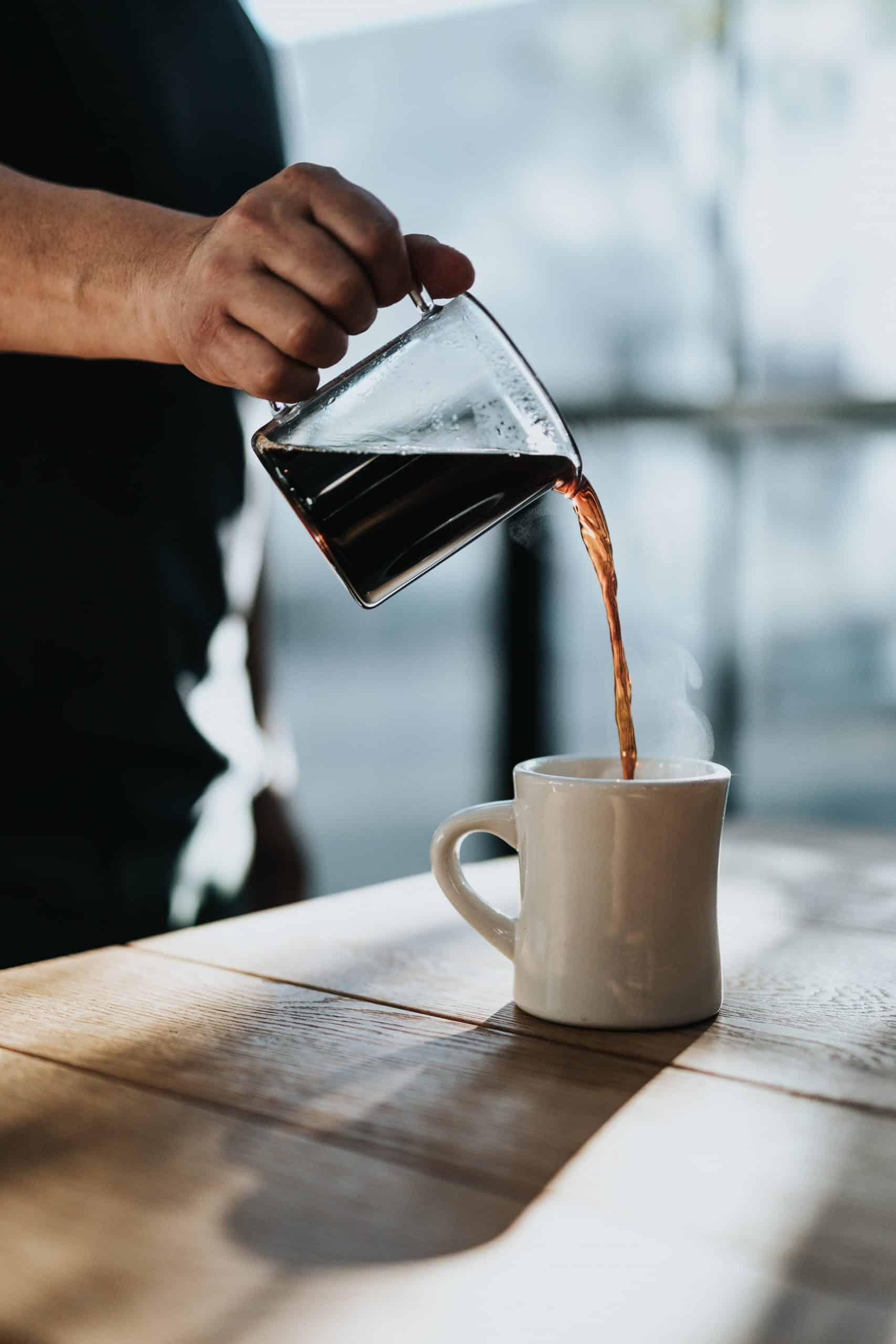 person pouring black coffee into white ceramic mug